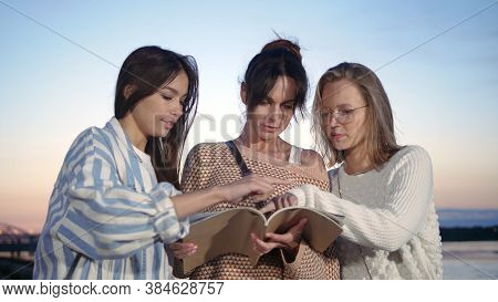 Three Women Friends Outside Looking Through Magazine.