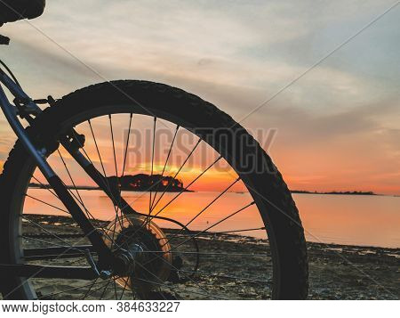 Beach at sunrise with bike wheel silhouette and water reflection