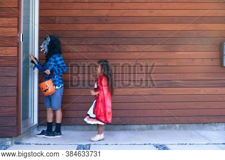 Two Children Wearing Fancy Dress Outside House Collecting Candy For Trick Or Treat