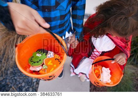 Close Up Of Two Children Wearing Fancy Dress Outside House Collecting Candy For Trick Or Treat
