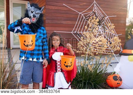 Portrait Of Two Children Wearing Fancy Dress Outside House Collecting Candy For Trick Or Treat