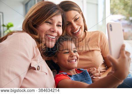 Multi-Generation Female Hispanic Family On Sofa At Home Posing For Selfie On Mobile Phone