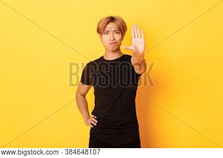 Portrait Of Disappointed Serious Asian Man, Smirking Displeased And Extend Hand, Showing Stop Gestur