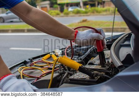 The Technician Uses A Booster Cable To Connect The Dead Battery. Electric Vehicle Battery Charging V