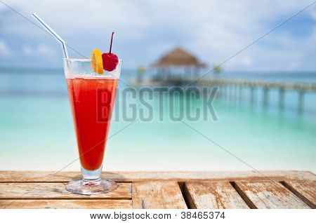 Red - orange drink over turquoise water