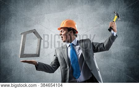 Businessman Going To Crash With Hammer House Symbol. Young Contractor In Business Suit And Safety He