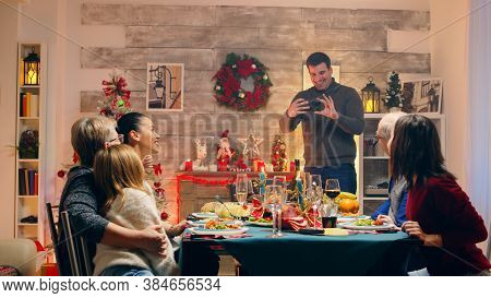 Adult Man Taking A Photo With The Family At Christmas Reunion. Happy Family. Winter Holidays. Tradit