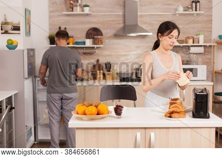 Housewife In Pajamas Preparing Breakfast Making Roasted Bread On Electric Toaster. Young Couple In T