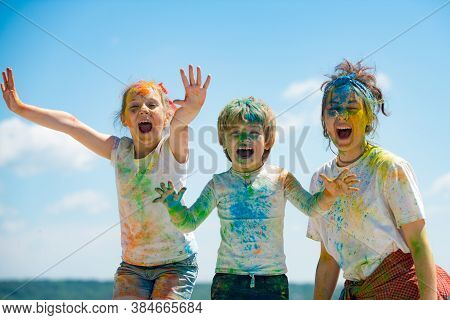 Funny Kids Face In Color Splash, Coloured Powder On Children Body. Cheerful Friends Showing Hands Pa