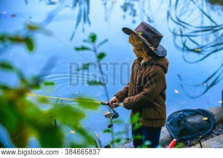Little Boy Fishing In Overalls From A Dock On Lake Or Pond. Child With A Fishing Rod Standing By The