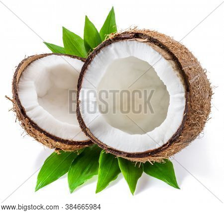 Split coconut fruit with white flesh over green leaves isolated on white background.