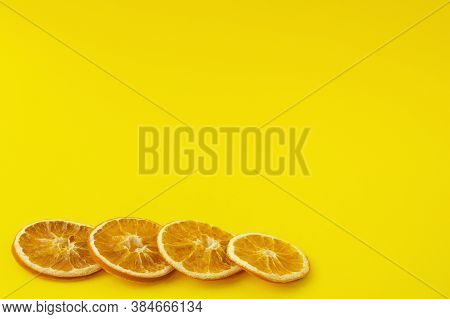 Dehydrated Dried Orange Slices On A Bright Yellow Background. Beautiful Background For Text, Copy Sp
