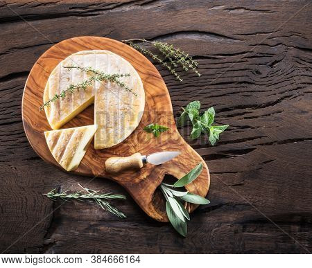 Head of brie cheese or raclette cheese with herbs on wooden table. Top view.
