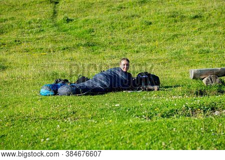 Young Woman Summerhiker With Backpack Lying In Her Sleeping Bag On Meadow After Hike. Female Trekke