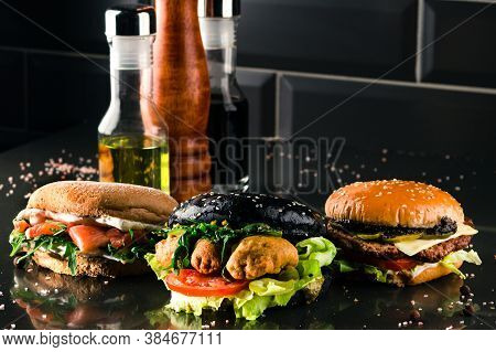 Three Burgers With Different Bread Buns On Dark Background, Different New Burgers Against Black Back