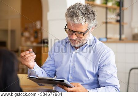 Focused Businessman Signing Agreement At Meeting. Mature Man In Shirt And Glasses Holding Notepad An