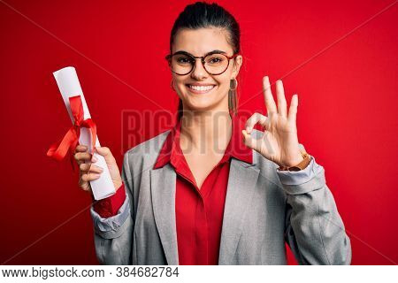 Young beautiful brunette student woman wearing glasses holding university degree diploma doing ok sign with fingers, excellent symbol