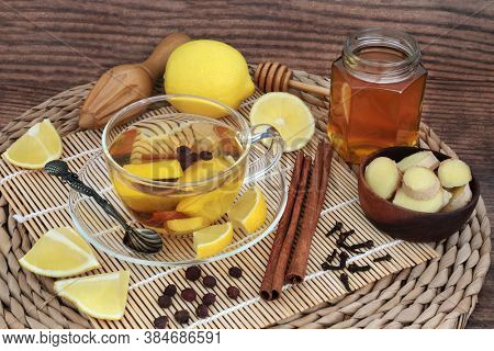 Traditional herbal remedy for colds & flu with hot drink of honey, lemon, cinnamon, ginger, cloves & hawthorn berries. Immune boosting health care for healing. On bamboo, wicker mat and rustic wood.