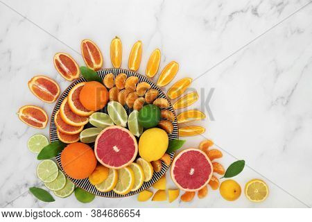 Citrus fruit high in antioxidants & vitamin c, with oranges, lemons, limes , mandarins & grapefruit on plates. Also high in anthocyanins, lycopene and dietary fibre. Health care concept. On marble.