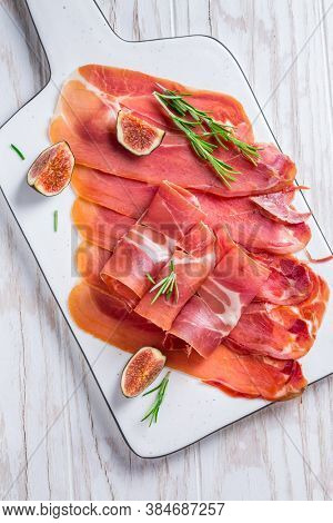 Delicious Serrano ham with fresh figs and rosemary on white cutting board