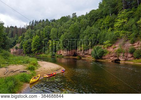 Landscape With Sandstone Cliffs, Canoes And Kayaks On The Gauja River Bank, Fast Flowing And Clear R
