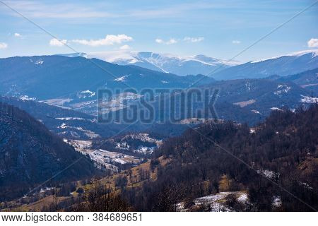 Mountainous Countryside In Early Spring. Dry Grass And Leafless Trees On The Hillside. Snow In The D