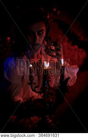 Portrait of vampire aristocrat in dim candlelight in a night castle. The style of the 19th century. Halloween.