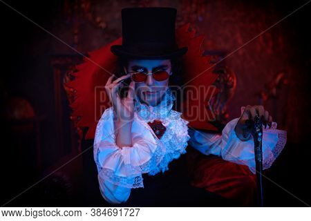 Portrait of a handsome vampire aristocrat of the 19th century in an elegant suit and with a drop of blood on his lips in his old castle. Count Dracula. Halloween.
