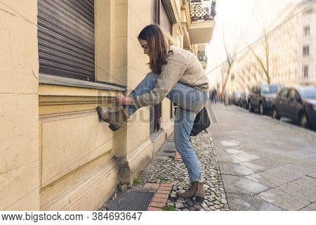 Young Woman Ties Her Shoe On The Street