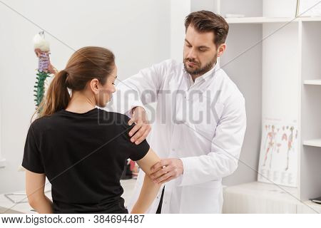 Male Doctor Examining Female Patient Suffering From Elbow Pain. Medical Exam. Chiropractic, Osteopat