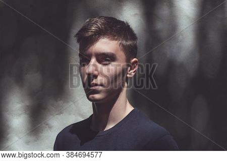 Portrait Of A Self-confident Young Man Standing In The Shadow