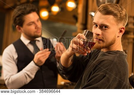 Young Bearded Handsome Man Looking To The Camera Fiercely Drinking Whiskey At The Barbershop Profess
