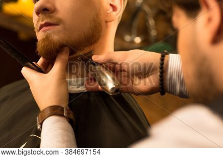 Cropped Close Up Of A Bearded Man Having His Beard Trimmed By A Professional Barber Using Trimmer Cl