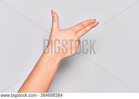 Hand of caucasian young woman gesturing fire gun weapon with fingers, aiming shoot symbol