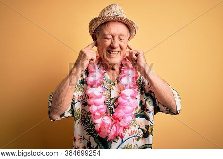 Grey haired senior man wearing summer hat and hawaiian lei over yellow background covering ears with fingers with annoyed expression for the noise of loud music. Deaf concept.