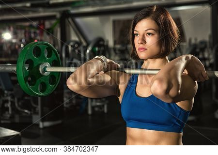 Strong Is Beautiful. Beautiful Young Female Athlete Working Out With Heavy Barbell At The Gym Weight