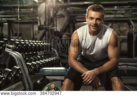After Gym Session. Cheerful Handsome Young Fitness Man Sitting Relaxed At The Gym After His Workout