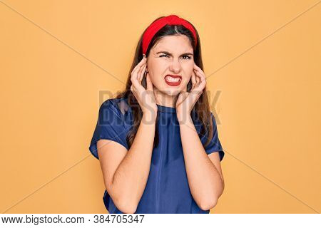 Young beautiful brunette woman wearing red lips over yellow background covering ears with fingers with annoyed expression for the noise of loud music. Deaf concept.