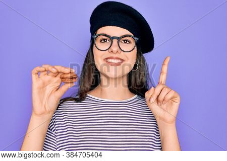 Young beautiful girl wearing glasses and fashion beret holding french sweet pastry macaron surprised with an idea or question pointing finger with happy face, number one