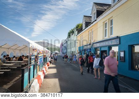 Portree, Isle Of Skye, Scotland - August 19, 2020: People Walking At Portree Harbour Promenade And E