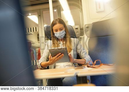 Businesswoman commuting by train, working on digital tablet and wearing face mask