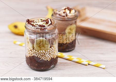 Layered Healthy Dessert With Banana Fruit Slices, Puffed Quinoa Grain And Chocolate Chia Seed Puddin