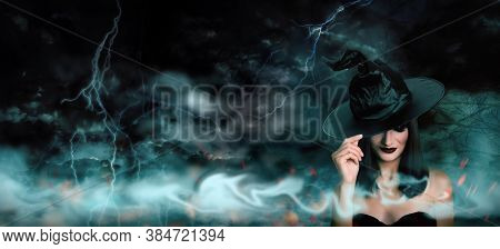 Young Girl Dressed As Witch In Misty Forest On Stormy Night. Halloween Fantasy