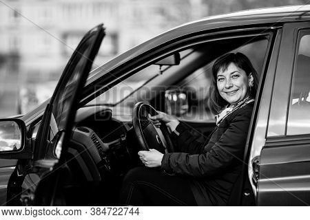 A woman in his new car. Black and white photo.