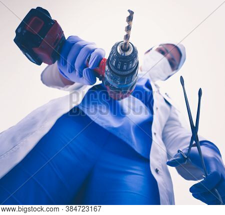 View From Below Of Masked Doctor Scaring The Patient With A Drill .