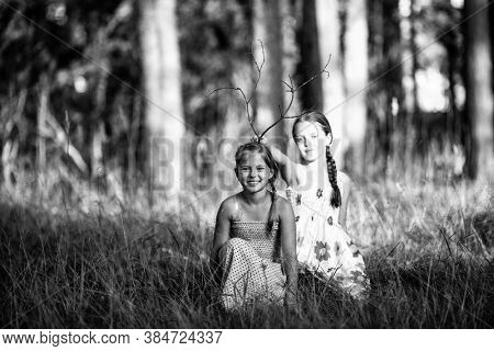 Two ten year old girls pose for a photo in the park. Black and white photo.