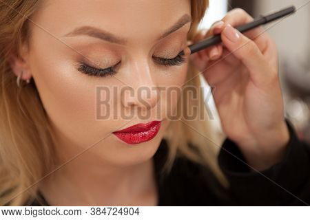 Close Up Of A Professional Makeup Artist Lining Eyes Of A Beautiful Woman With Kajal