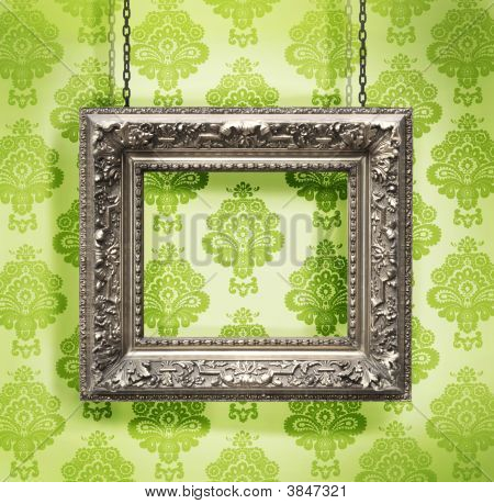 Silver Picture Frame Hung Against Floral Wallpaper