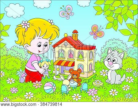 Cute Little Girl Playing With A Small Doll, A Bear, A Rabbit And A Toy House Among Flowers On A Sunn