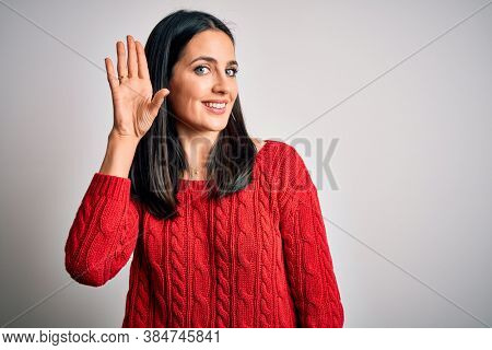Young brunette woman with blue eyes wearing casual sweater over isolated white background Waiving saying hello happy and smiling, friendly welcome gesture